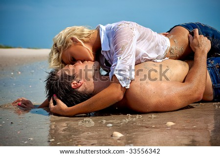 Happy young couple at the beach kissing.