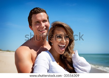 Happy young couple at the beach smiling - stock photo