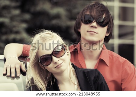 Happy young couple at the car  - stock photo