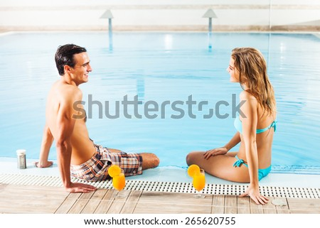 Happy young couple at the swimming pool - stock photo