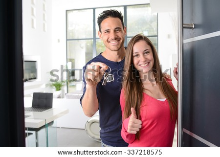happy young couple at their new house front door proud to show home keys - stock photo