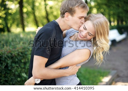 Happy young couple. Beautiful smiling blonde girl hugging her boyfriend in summer park. - stock photo