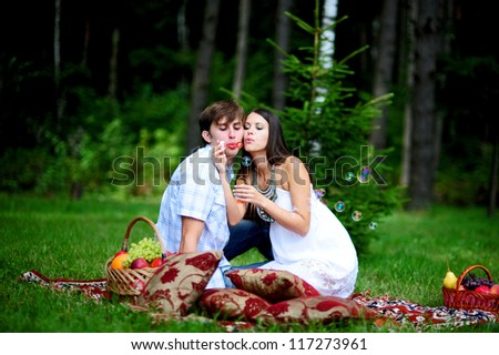 Happy young couple blow bubbles on picnic in park - stock photo