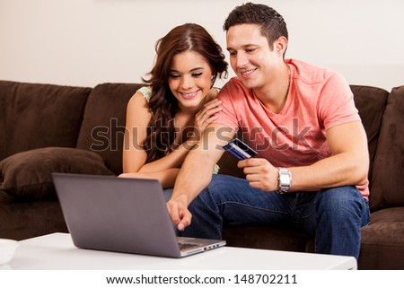 Happy young couple booking a vacation trip online together with a laptop computer and a credit card - stock photo
