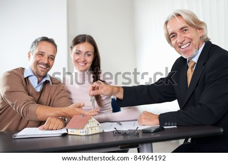 Happy young couple buying new home with agent - stock photo