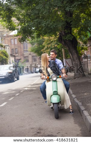 Happy young couple by a vintage scooter on the street. Holiday and travel concept