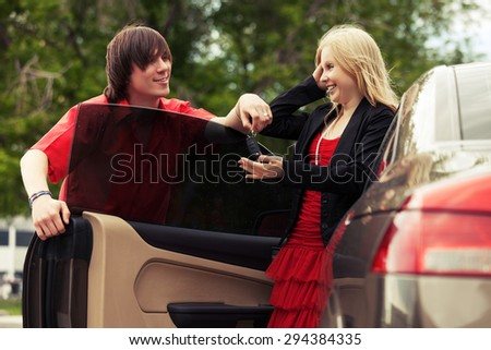 Happy young couple by new convertible car - stock photo