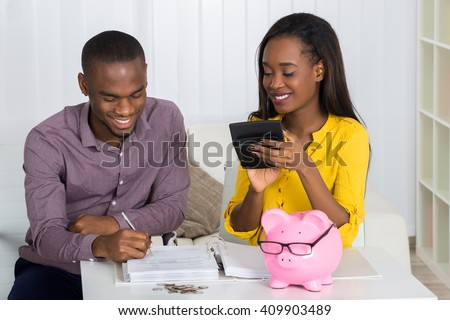 Happy Young Couple Calculating Bill With Coins And Piggybank On Desk - stock photo