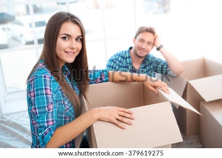Happy young couple carrying moving boxes. Young family holding and unpacking cardboard boxes while moving to new home. Woman and man smiling and looking at camera