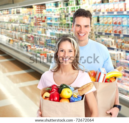 Happy young couple carrying shopping bags with food - stock photo