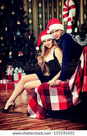 Happy young couple celebrating Christmas near the Christmas tree and fireplace at home. - stock photo