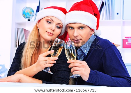 Happy young couple celebrating Christmas near the Christmas tree at home. - stock photo