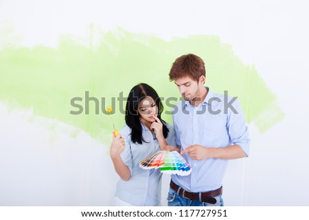 happy young couple choose palette color pantone paint in green color white wall of their new apartment home - stock photo
