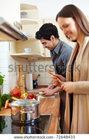 Happy young couple cooking a soup together in the kitchen - stock photo