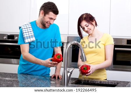 Happy young couple cooking together at home