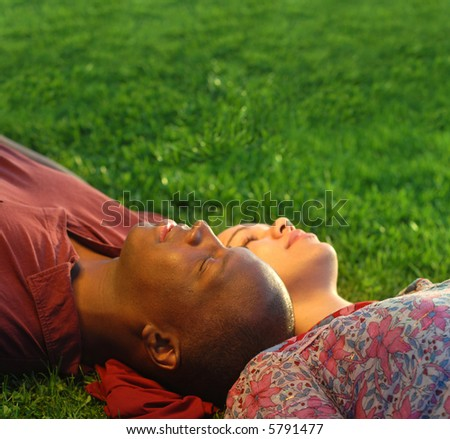 Happy young couple daydreaming together at the park on the grass - stock photo