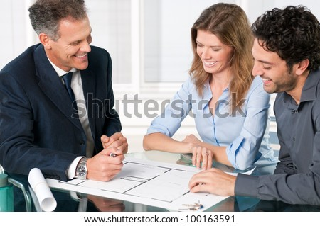 Happy young couple discussing with an estate agent about their new house plans - stock photo
