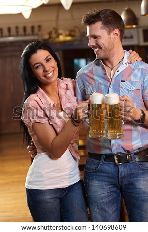 Happy young couple drinking beer in pub, clinking glasses, smiling. - stock photo
