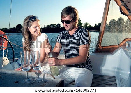 Happy young couple drinking champagne on yacht - stock photo