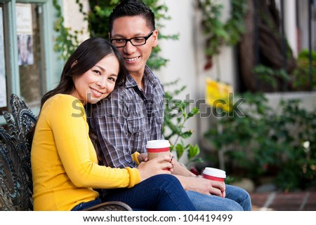 Happy young couple drinking coffee outside cafe - stock photo