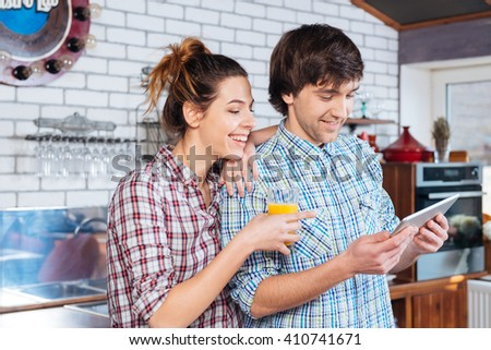 Happy young couple drinking fresh juice and using tablet on the kitchen  - stock photo