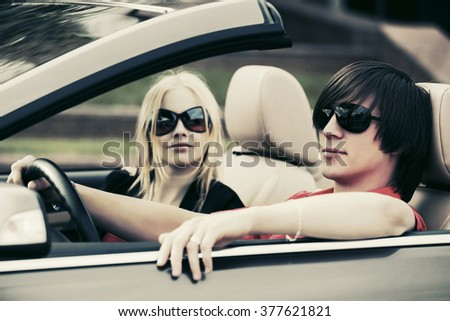 Happy young couple driving convertible car - stock photo
