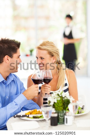 happy young couple eating out in restaurant - stock photo