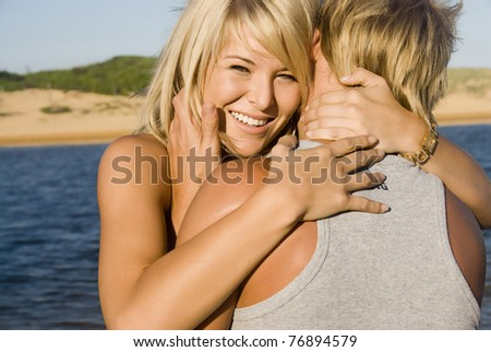 Happy young couple embrace at the beach - stock photo