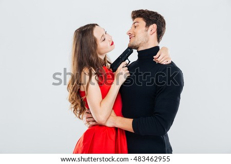 Happy young couple embracing and posing with gun