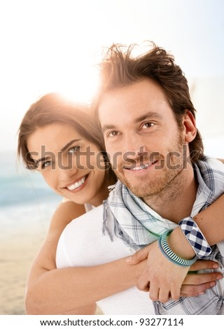 Happy young couple embracing on summer beach, having fun together, laughing.? - stock photo