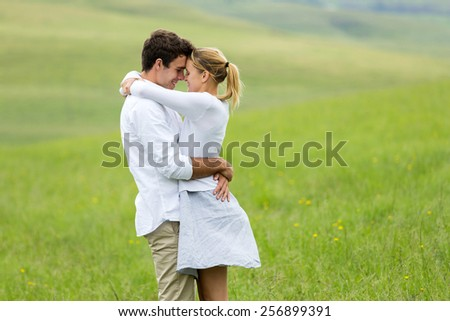 happy young couple embracing outdoors - stock photo