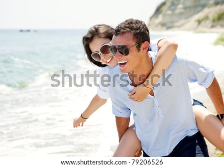 Happy young couple enjoying a solitary beach backriding - stock photo