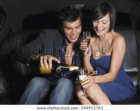Happy young couple enjoying champagne in limousine - stock photo