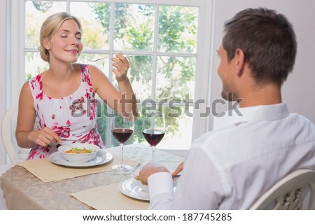 Happy young couple enjoying food at home - stock photo