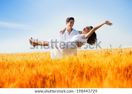 Happy young couple enjoying in the wheat field, summer season - stock photo