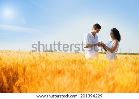 Happy, young couple enjoying in the wheat field, summer season .Sunset light, flare light ,copy space - stock photo