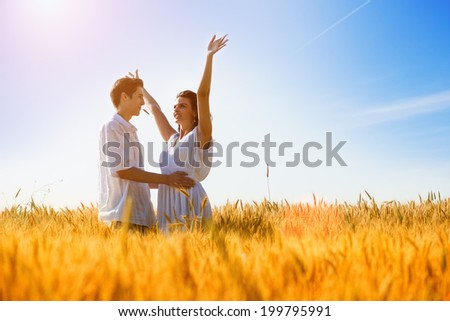 Happy young couple enjoying in the wheat field, summer season. Sunset light, flare light, copy space - stock photo