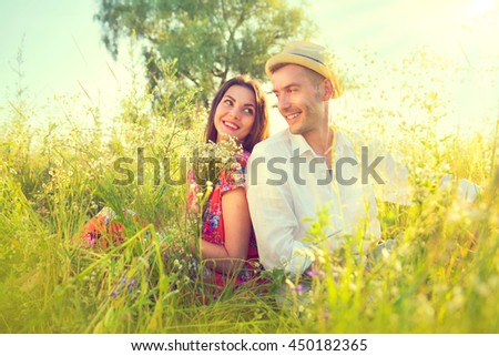 Happy Young Couple enjoying nature outdoors. Beautiful Girlfriend with her boyfriend sitting on summer field with bunch of wildflowers and smiling. Joyful people, vacation concept. - stock photo
