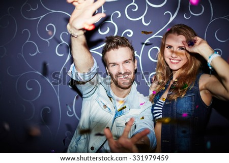 Happy young couple enjoying party in club - stock photo
