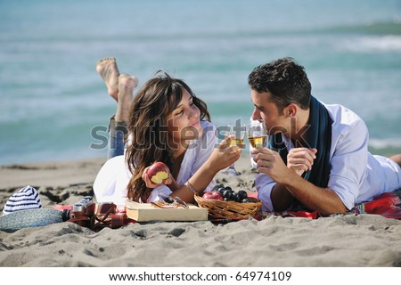happy young couple enjoying  picnic on the beach and have good time on summer vacations - stock photo