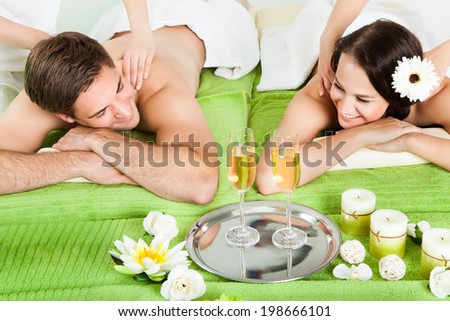 Happy young couple enjoying shoulder massage at beauty spa - stock photo