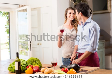 Happy Young Couple Enjoying Wine While Working In Kitchen - stock photo