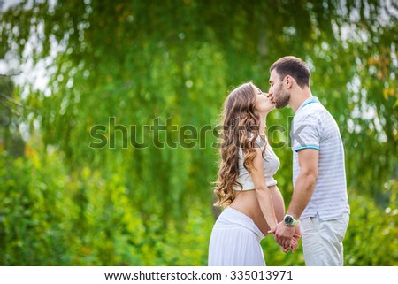 Happy young couple expecting baby in summer park - stock photo