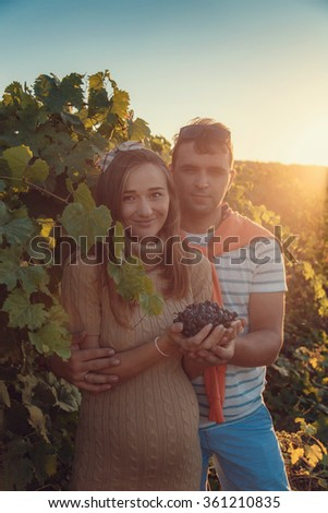 Happy young couple expecting baby, pregnant woman with husband touching belly. Happy and young pregnant couple hugging in nature