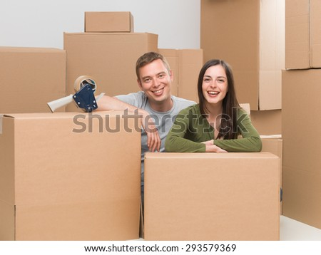 happy young couple finishing packing, getting ready to move house - stock photo