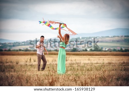 happy young couple flying a kite - stock photo