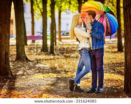 Happy young couple full height kissing under umbrella in autumn day. Love and couple relationships concept . - stock photo