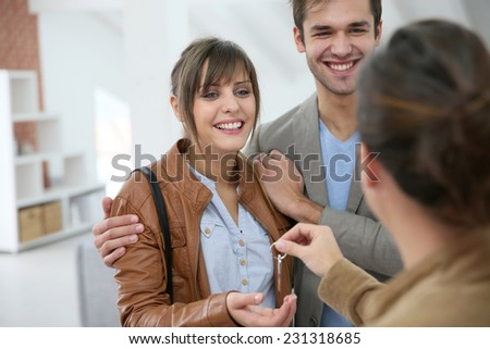 Happy young couple getting key of their new place - stock photo