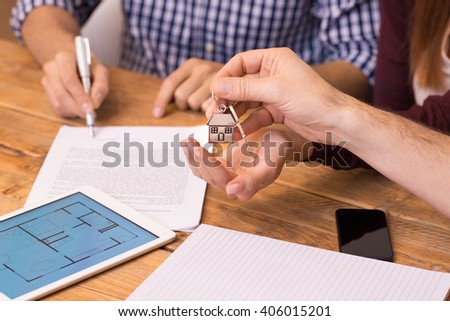 Happy young couple getting keys of their new house. Closeup of the hand of a real estate agent who give the house keys to a woman while her boyfriend signing a contract. - stock photo
