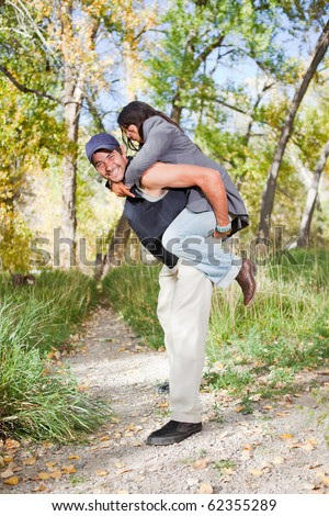 Happy young couple, girlfriend on piggyback. Shallow DOF, guy's face is the focus point. - stock photo